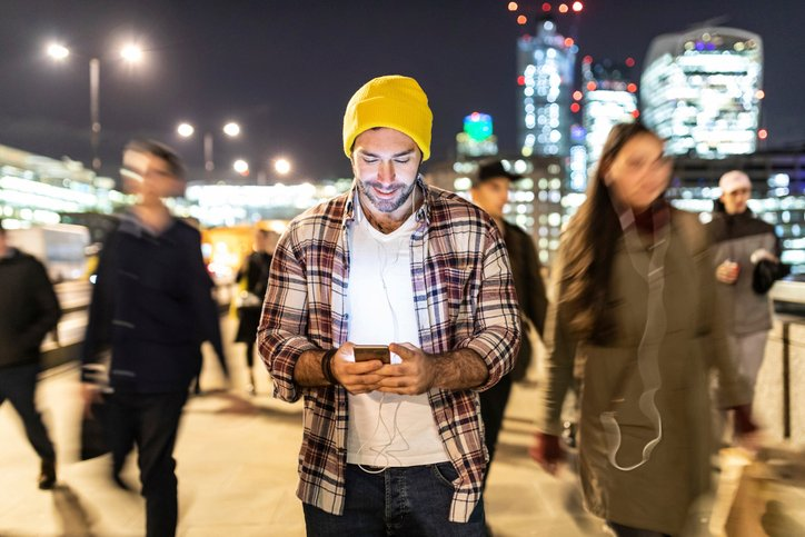 A man shops on a smart phone in a crown in Europe.