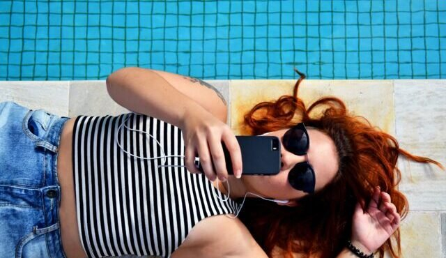 A woman in sunglasses using an in-app payment solution to make a purchase by a pool.