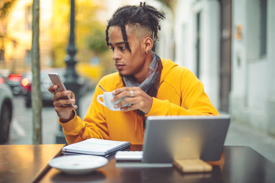 A young man uses an online payment method while sitting outside at a cafe.