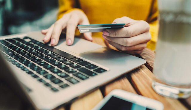 Chargeback Fraud: Woman's hands holding credit card and typing