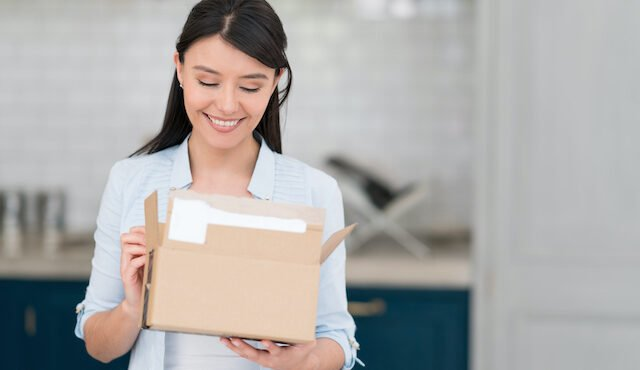 Woman getting a package on the mail from a subscription payment business.