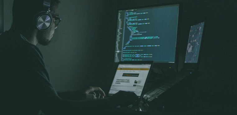 developer sitting at computer coding python for his ecommerce website and listening to music