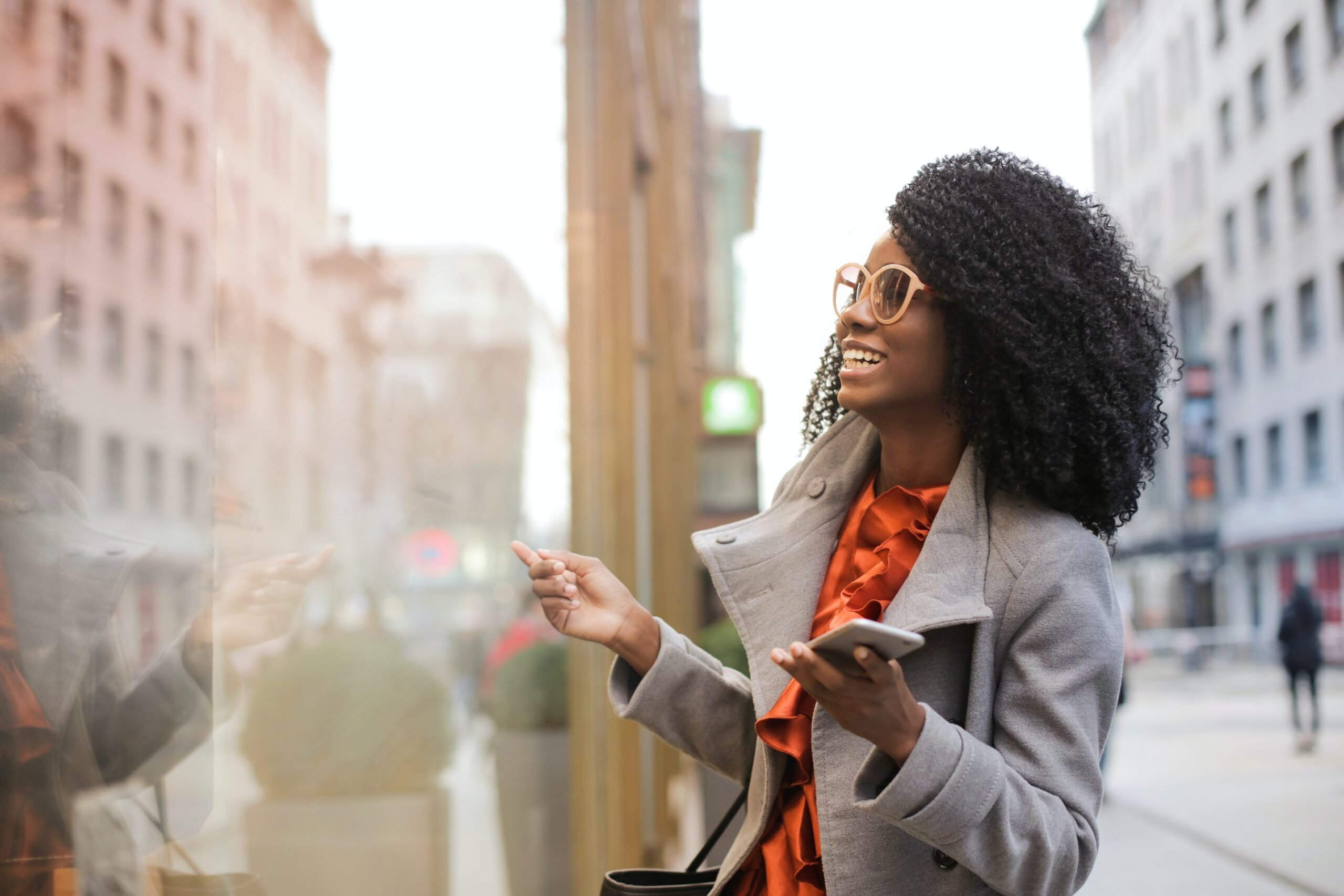 Woman in glasses holds phone in city