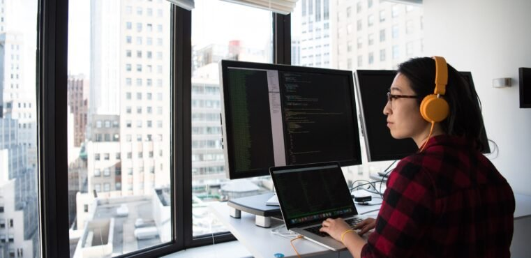 Woman programmer codes at a standing desk overlooking the city